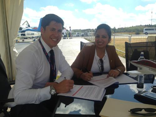 Adam Hahn, director of sales for Cirrus Aircraft; and Roohi Bali, sales manager for Cirrus India, signing contract.