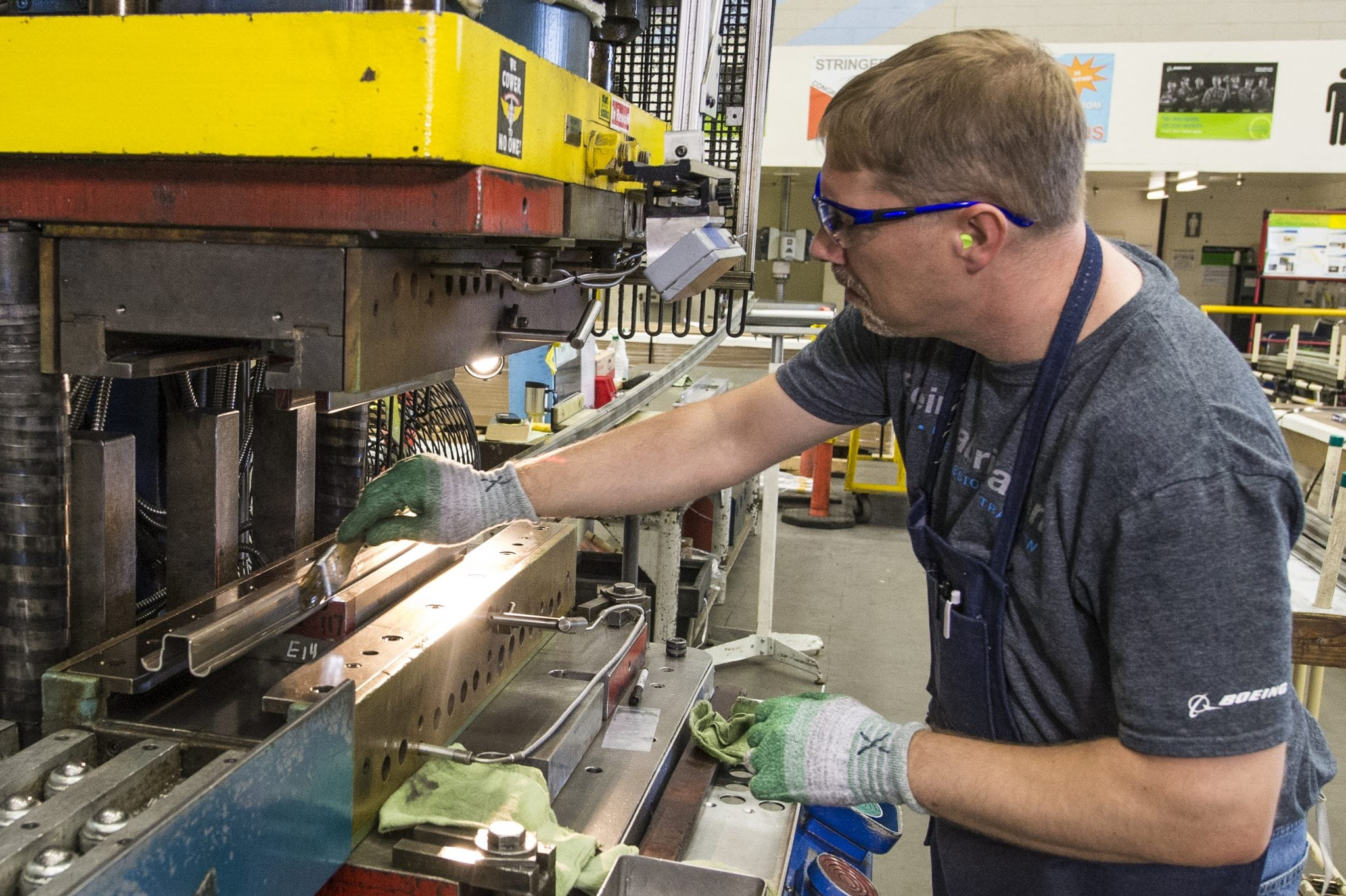Joggle Press operator Rich Harrison prepares the first 737 MAX fuselage stringer for the press