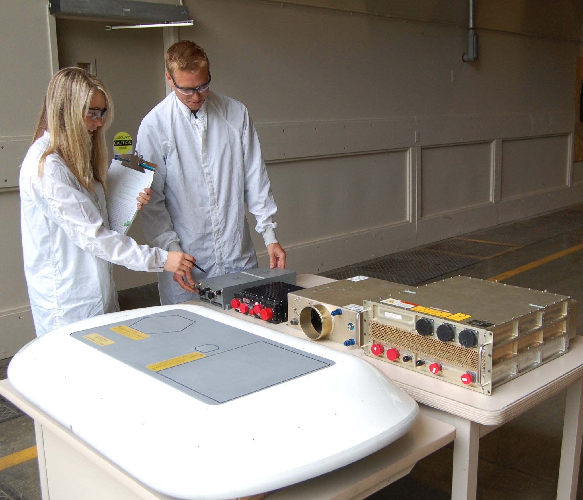 Boeing engineers Stephanie Mount and Chuck Renneberg examine the low-profile phased array antenna