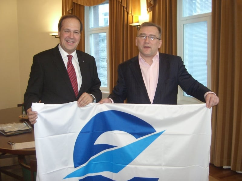 Frank Brenner, director general of Eurocontrol, and Juhan Parts, the Estonian minister for economic affairs and communications hold a flag bearing the Eurocontrol logo