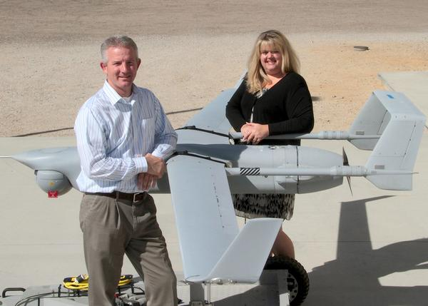 James Bell and Deidre Patin stand next to an unmanned aerial vehicle at Naval Air Warfare Center Weapons Division China Lake, Calif.