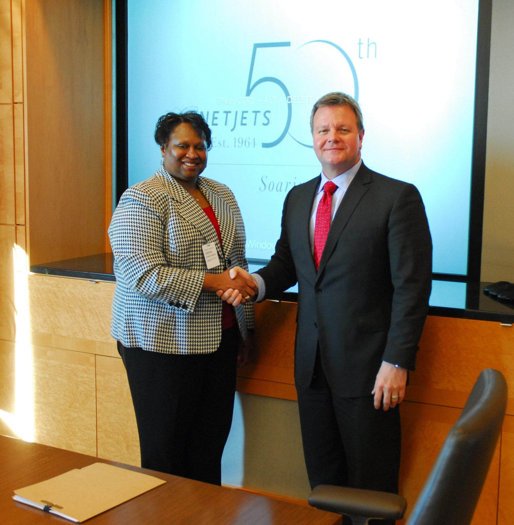 FAA Deputy Administrator for NextGen Pamela Whitley and NetJets Global Chief Operating Office and President of NetJets Aviation Bill Noe shake hands after signing new five year agreement for development and implementation of NextGen projects