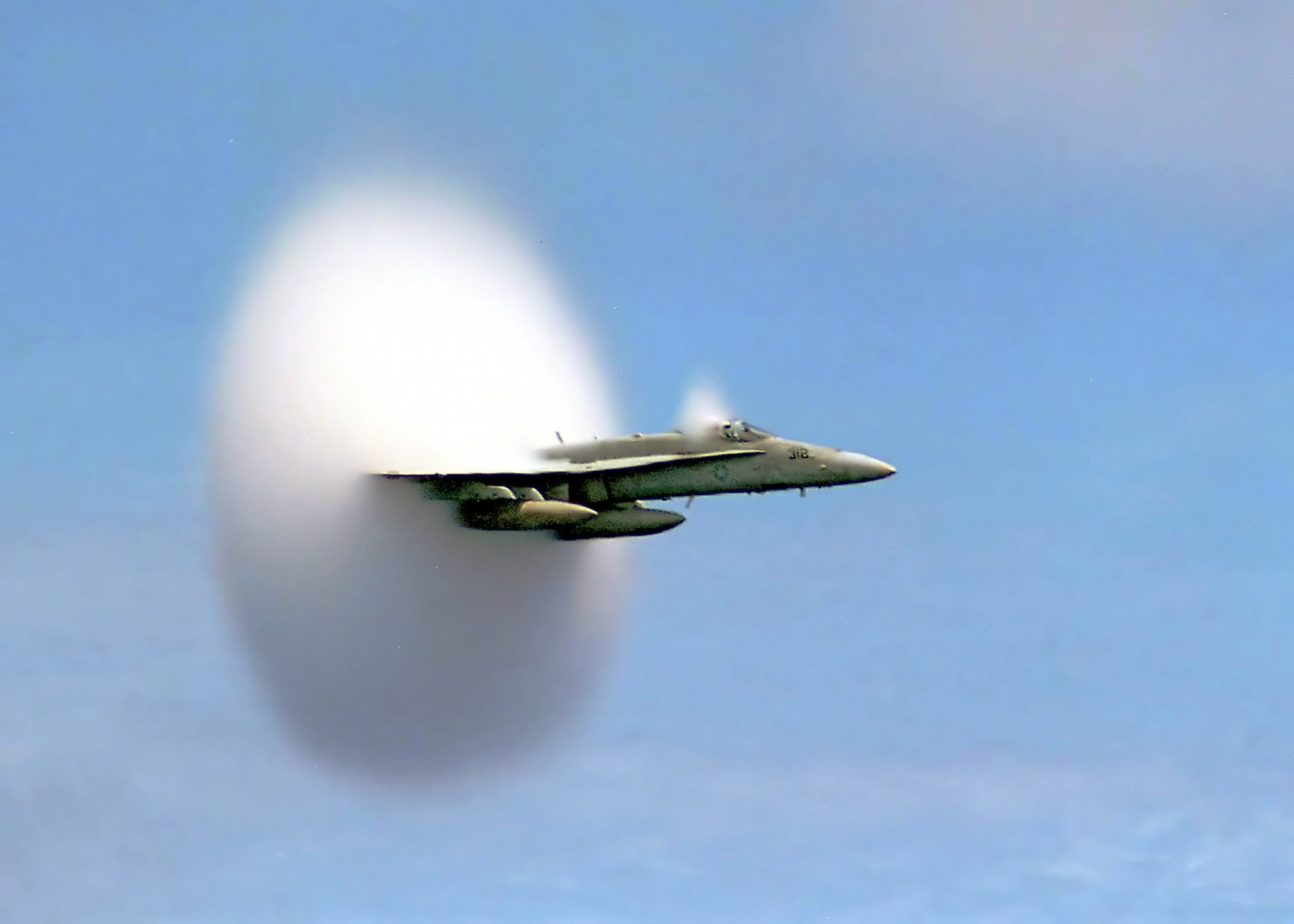 U.S. Navy F/A-18 approaching the sound barrier. The white halo is formed by condensed water droplets which result from the shock wave shedding from the aircraft.