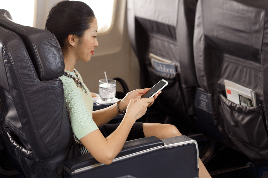 Airline passenger accesses in-flight Wi-Fi on her smartphone