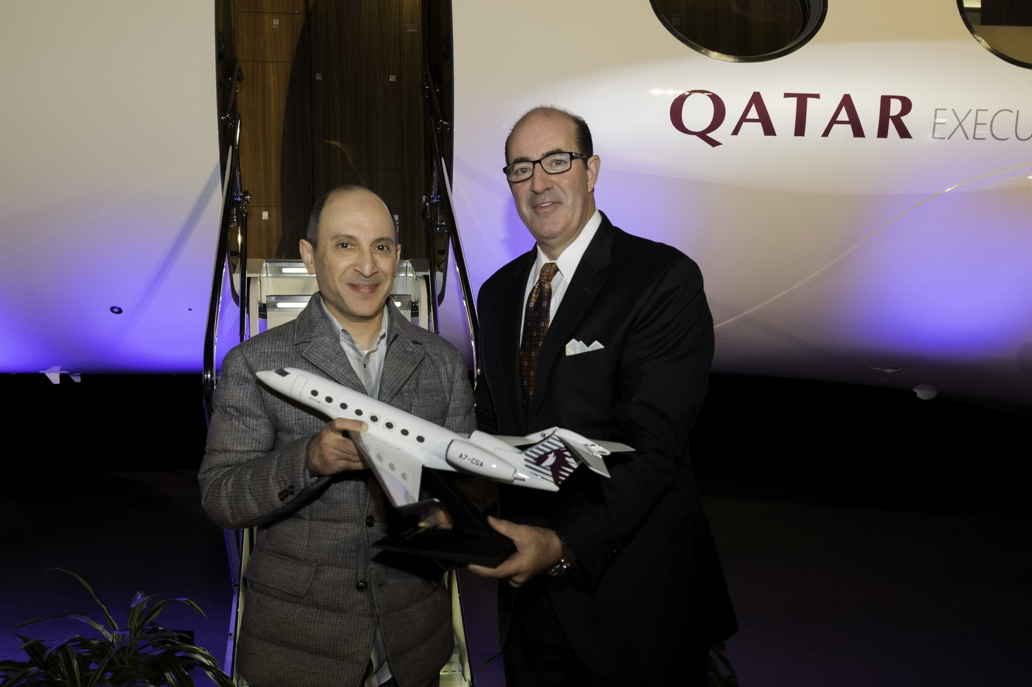 Qatar Airways Group Chief Executive Akbar Al Bakerreceives an aircraft model fromMark Burns, president, Gulfstream