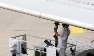 Airline workers re-fueling jet plane