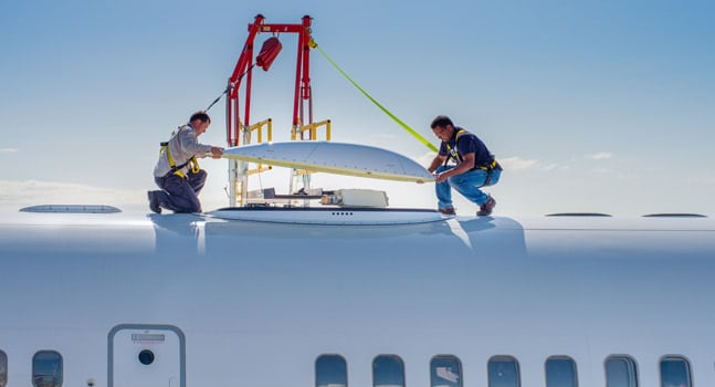 Technicians install GX Aviation antenna on aircraft