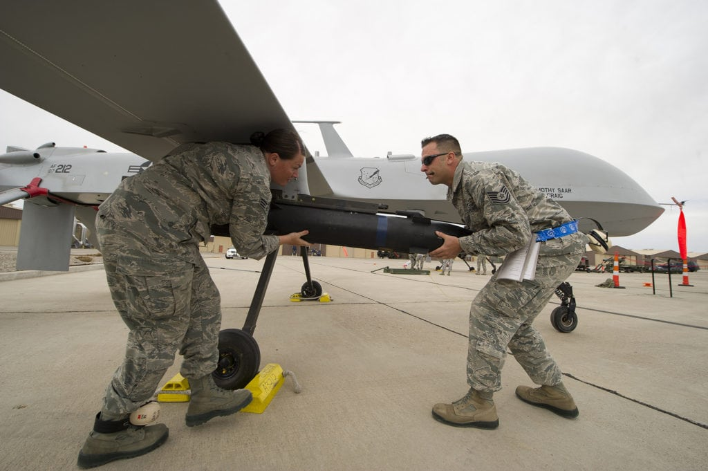 Senior Airman Bethany Lamb and Tech. Sgt. Travis Wheeler load an inert missile onto a MQ-1 Predator during a load crew competition April 5 at Holloman Air Force Base, N.M. Load crew competitions are held on a quarterly basis to help build morale through friendly competition. Lamb and Wheeler are 849th Aircraft Maintenance Squadron load crew members. (U.S. Air Force photo by Airman 1st Class Michael Shoemaker)